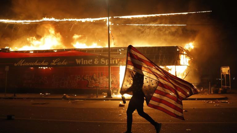 A protester carries a U.S. flag upside down, a sign of distress, next to a burning building Thursday, May 28, 2020, in Minneapolis. (AP Photo / Julio Cortez)