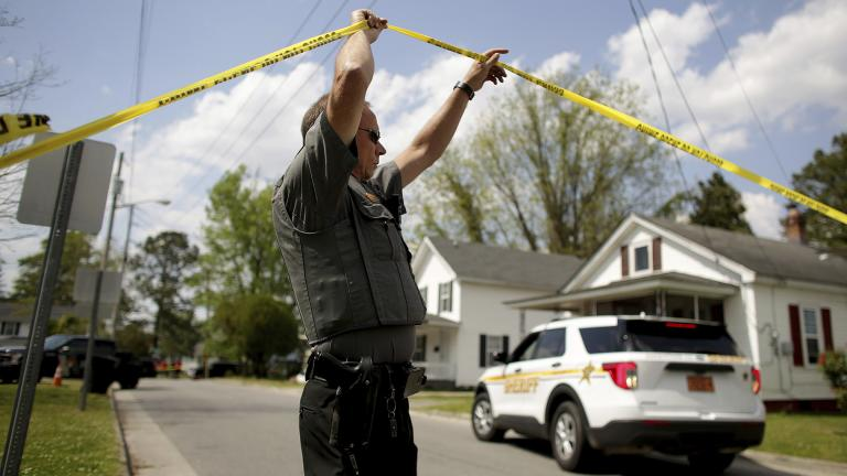 Law enforcement investigate the scene of a shooting, Wednesday, April 21, 2021 in Elizabeth City, N.C. At least one law enforcement officer with a sheriff's department in North Carolina shot and killed a man while executing a search warrant Wednesday, the sheriff's office said. (Stephen M. Katz / The Virginian-Pilot via AP)
