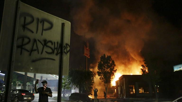 """RIP Rayshard"" is spray painted on a sign as flames engulf a Wendy's restaurant during protests Saturday, June 13, 2020, in Atlanta. (AP Photo / Brynn Anderson)"
