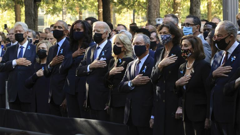 (L-R)  former President Bill Clinton, former First Lady Hillary Clinton, former President Barack Obama, former First Lady Michelle Obama, President Joe Biden, First Lady Jill Biden, former New York City Mayor Michael Bloomberg, Bloomberg's partner Diana Taylor, Speaker of the House Nancy Pelosi and Senate Minority Leader Charles Schumer stand for the national anthem during the annual 9/11 Commemoration Ceremony at the National 9/11 Memorial and Museum Sept. 11, 2021 in New York. (Chip Somodevilla / AP)