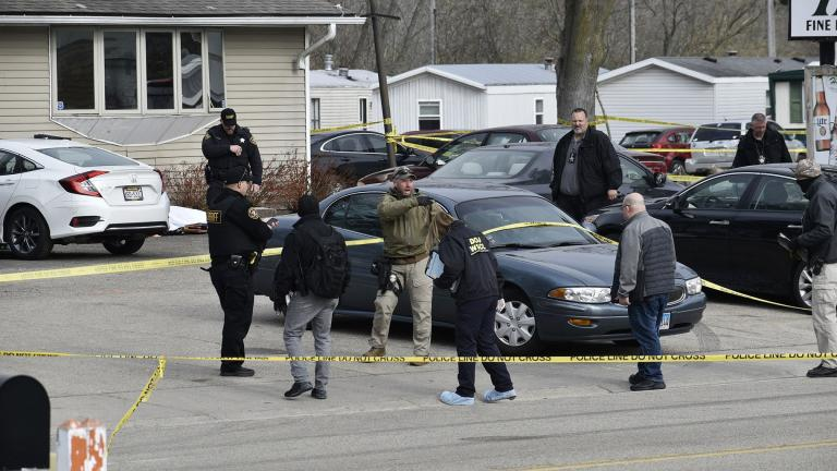 Investigators confer during an investigation outside the Somers House Tavern, in Kenosha, Wis., Sunday morning, April 18, 2021. (Deneen Smith / The Kenosha News via AP)