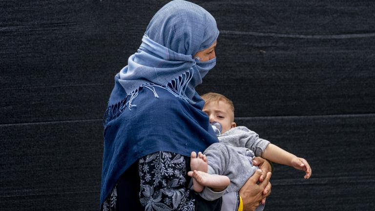 A woman evacuated from Afghanistan steps off a bus with a baby as they arrive at a processing center in Chantilly, Monday, Aug. 23, 2021, after arriving on a flight at Dulles International Airport. (AP Photo / Andrew Harnik)