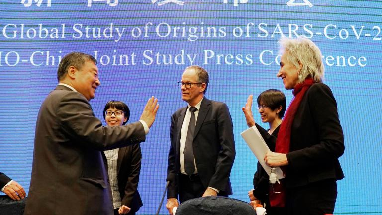 Marion Koopmans, right, and Peter Ben Embarek, center, of the World Health Organization team say farewell to their Chinese counterpart Liang Wannian, left, after a WHO-China Joint Study Press Conference held at the end of the WHO mission in Wuhan, China, Tuesday, Feb. 9, 2021. (AP Photo / Ng Han Guan)