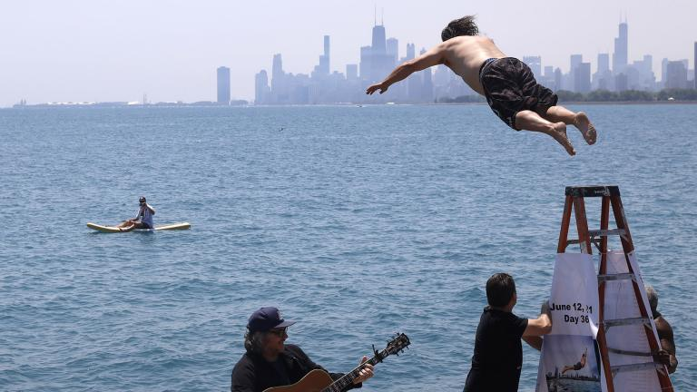 """Dan O'Conor, the """"Great Lake Jumper,"""" makes his 365th leap into Lake Michigan, Saturday, June 12, 2021, in Chicago's Montrose Point. (AP Photo / Shafkat Anowar)"""