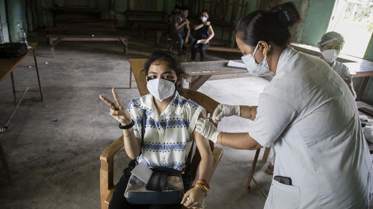 An Indian woman getting vaccinated with a dose of COVAXIN against the coronavirus gestures to camera in Gauhati, Assam, India, Monday, May 10, 2021. (AP Photo / Anupam Nath)