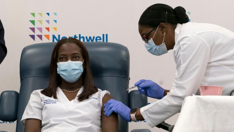 Sandra Lindsay, left, a nurse at Long Island Jewish Medical Center, is inoculated with the Pfizer-BioNTech COVID-19 vaccine by Dr. Michelle Chester, Monday, Dec. 14, 2020, in the Queens borough of New York. (AP Photo / Mark Lennihan, Pool)