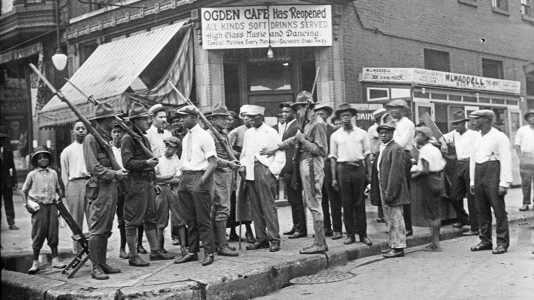 In this 1919 photo provided by Chicago History Museum, a crowd of men and armed National Guard stand in front of the Ogden Cafe during race riots in Chicago. (Chicago History Museum / The Jun Fujita negatives collection via AP)