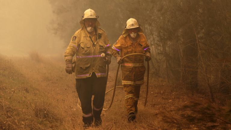 Firefighters drag their water hose after putting out a spot fire near Moruya, Australia, Saturday, Jan. 4, 2020. Australia's Prime Minister Scott Morrison called up about 3,000 reservists as the threat of wildfires escalated Saturday in at least three states with two more deaths, and strong winds and high temperatures were forecast to bring flames to populated areas including the suburbs of Sydney. (AP Photo / Rick Rycroft)