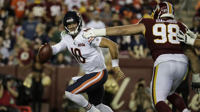 Chicago Bears quarterback Mitchell Trubisky (10) works to escape Washington Redskins defensive end Matthew Ioannidis (98) during the second half of an NFL football game Monday, Sept. 23, 2019, in Landover, Md. (AP Photo / Julio Cortez)