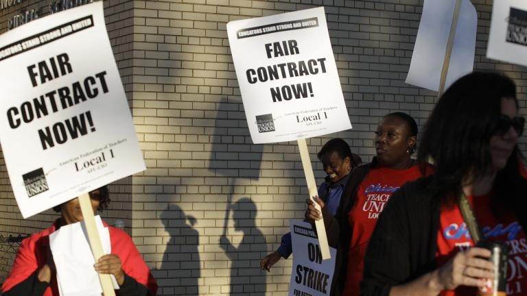 This Sept. 10, 2012 file photo shows Chicago teachers walking a picket line outside a school in Chicago, after they went on strike for the first time in 25 years. (AP Photo / M. Spencer Green, File)