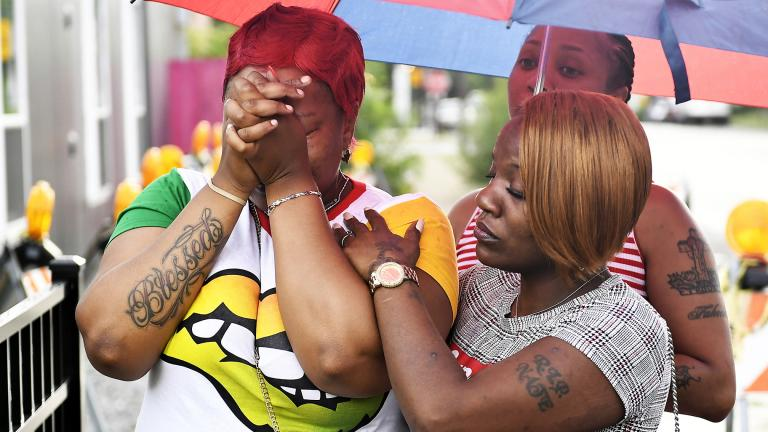 Charvonda Andrews is consoled Tuesday, July 30, 2019 in Chicago as she mourns two women killed July 26 while working as volunteers with a group called Mothers Against Senseless Killings. (John Alexander / Chicago Sun-Times via AP)