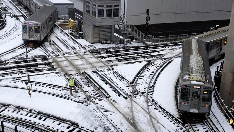 CTA trains move along snow-covered tracks Monday, Jan. 28, 2019, in Chicago. (AP Photo / Kiichiro Sato)
