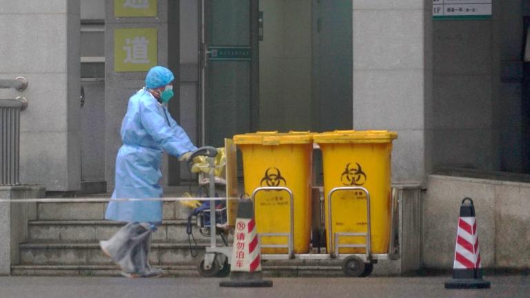 In this Wednesday, Jan. 22, 2020, file photo, a staff member moves bio-waste containers past the entrance of the Wuhan Medical Treatment Center in Wuhan, China, where some people infected with a new virus are being treated. (AP Photo / Dake Kang, File)