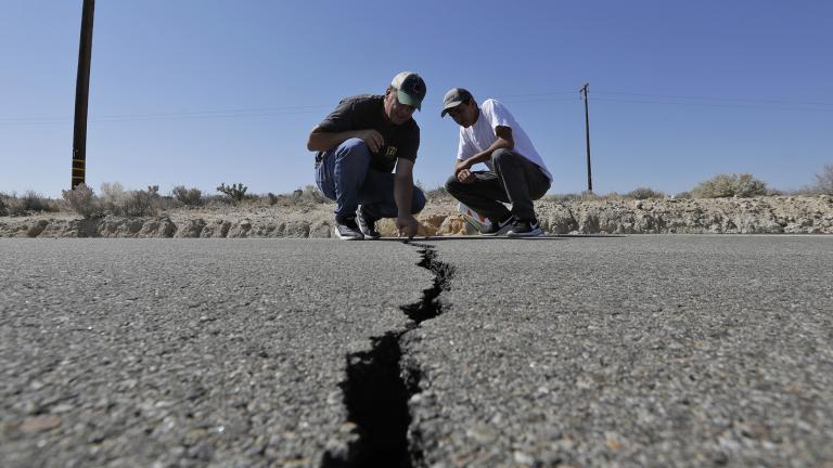 Ron Mikulaco, left, and his nephew, Brad Fernandez, examine a crack on Highway 178 caused by an earthquake Saturday, July 6, 2019, outside of Ridgecrest, California. (AP Photo / Marcio Jose Sanchez)