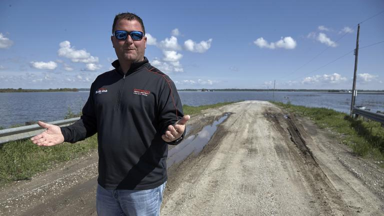 In this May 10, 2019 photo, Brett Adams gestures as he stands where the road to his flooded farm disappears under flood waters, with the farm buildings seen in the background, in Peru, Neb. (AP Photo / Nati Harnik)
