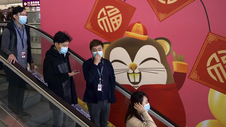 People wear face masks as they ride an escalator at the Hong Kong International Airport in Hong Kong, Tuesday, Jan. 21, 2020. (AP Photo / Ng Han Guan)