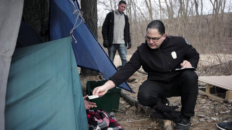 In this Tuesday, Feb. 12, 2019 file photo, Worcester Police Officer Angel Rivera, right, returns a license to an unidentified man as Rivera asks if he has been tested for Hepatitis A at the entrance to a tent where the man spent the night in a wooded area, in Worcester, Mass. (AP Photo / Steven Senne)