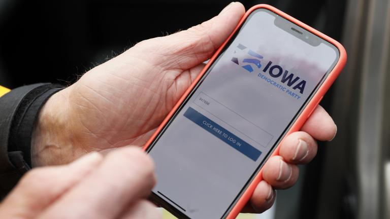 Precinct captain Carl Voss, of Des Moines, Iowa, holds his iPhone that shows the Iowa Democratic Party's caucus reporting app Tuesday, Feb. 4, 2020, in Des Moines, Iowa. (AP Photo / Charlie Neibergall)