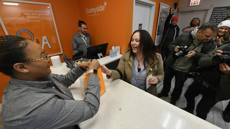 Jackie Ryan, right, of Forest Park, Ill., becomes the first person in Illinois to purchase recreational marijuana as she purchases marijuana products from employee Brea Mooney left, at Sunnyside dispensary Wednesday, Jan. 1, 2020, in Chicago. (AP Photo / Paul Beaty)