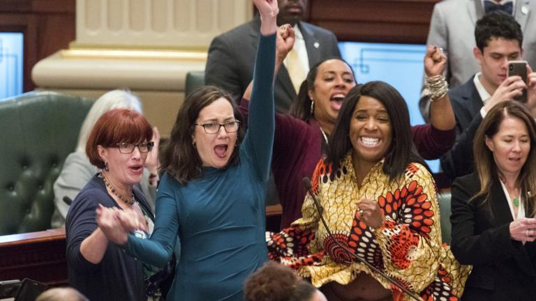 Illinois state Rep. Kelly Cassidy, D-Chicago, throws her fist in the air as she celebrates with Illinois state Sen. Heather Steans, D-Chicago, left, and Rep. Jehan Gordon-Booth, D-Peoria, as they watch the final votes come in for their bill to legalize recreational marijuana use in the Illinois House chambers Friday, May 31, 2019. The 66-47 vote sends the bill to Gov. J.B. Pritzker who indicated he will sign it. (Ted Schurter / The State Journal-Register via AP)