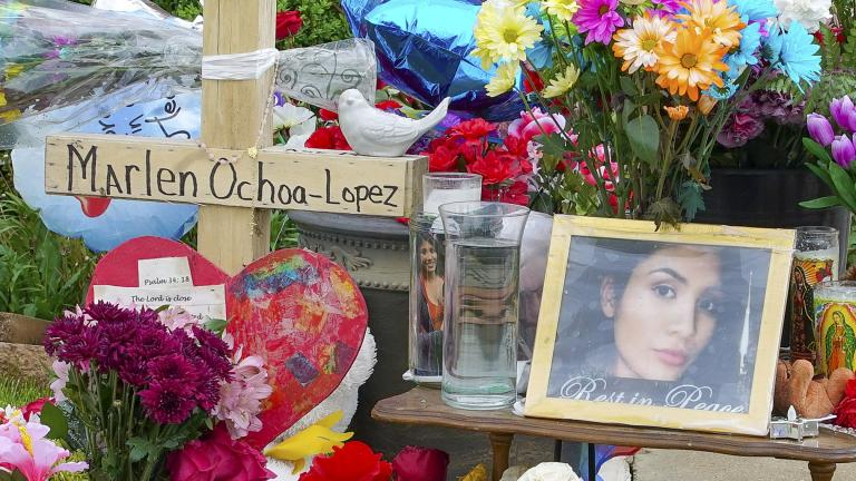 A memorial of flowers, balloons, a cross and photo of Marlen Ochoa-Lopez are displayed on the lawn, Friday, May 17, 2019 in Chicago, outside the home where Ochoa-Lopez was murdered last month. (AP Photo / Teresa Crawford)