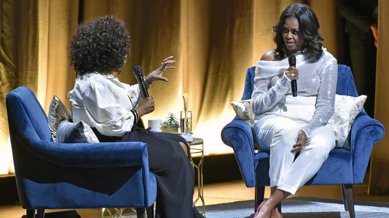 "Michelle Obama, right, discusses her new book with Oprah Winfrey during an intimate conversation to promote ""Becoming"" at the United Center on Tuesday, Nov. 13, 2018. (Photo by Rob Grabowski / Invision / AP)"
