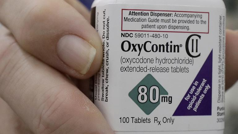 In this April 2, 2018, file photo, a pharmacist in San Francisco poses for photos holding a bottle of OxyContin. (AP Photo / Jeff Chiu, File)