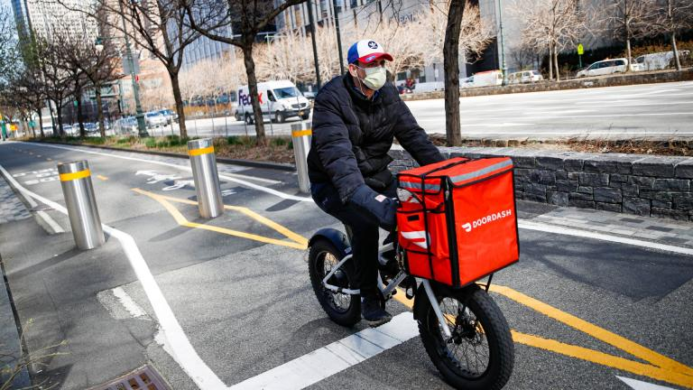 In this March 16, 2020 file photo, a delivery worker rides his bicycle along a path on the West Side Highway in New York. (AP Photo / John Minchillo, File)