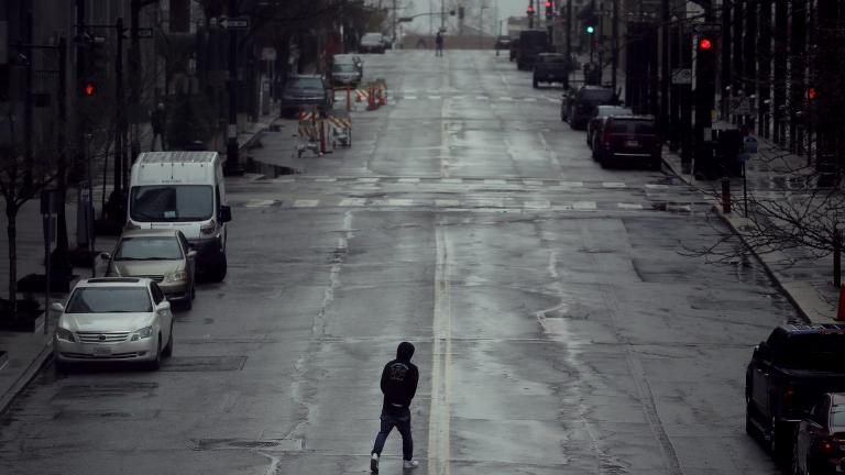 In this April 3, 2020, file photo a man crosses an empty street in downtown Kansas City, Missouri. (AP Photo / Charlie Riedel, File)