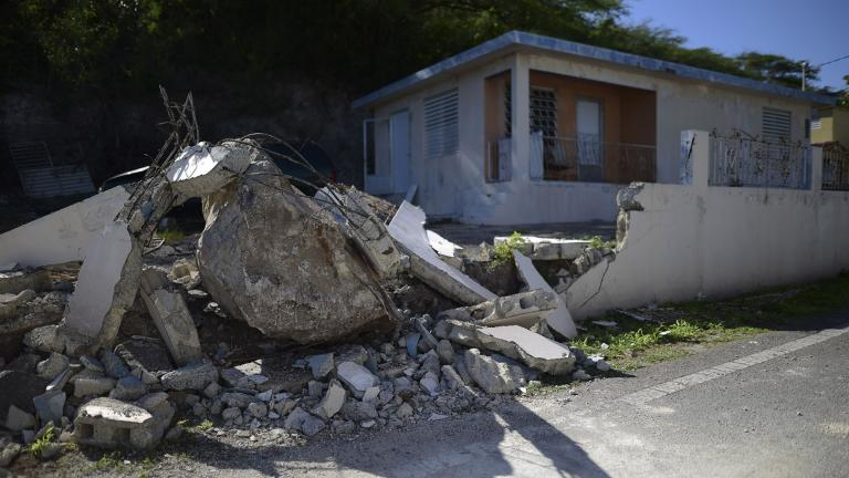 A big rock sits amid the rubble of the low wall it destroyed when it rolled down from a nearby cliff during a magnitude 5.9 earthquake in Guanica, Puerto Rico, Saturday, Jan. 11, 2020. (AP Photo / Carlos Giusti)