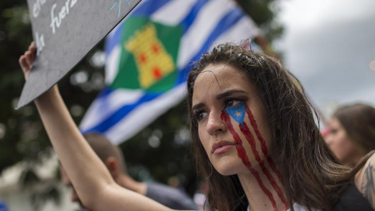In this July 25, 2019 photo, a young woman takes part in the festivities to celebrate the resignation of Gov. Ricardo Rossello, after weeks of protests over leaked obscene, misogynistic online chats, in San Juan, Puerto Rico. (AP Photo / Dennis M. Rivera Pichardo)
