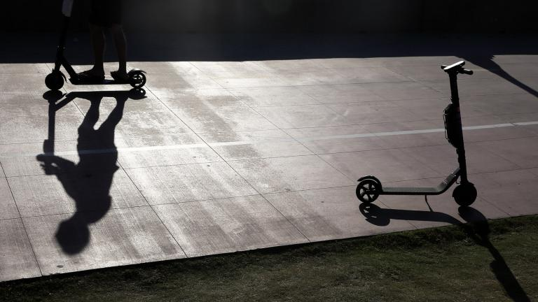In this May 28, 2019, file photo, a man on a scooter passes a parked scooter along the Mission Beach boardwalk in San Diego. (AP Photo / Gregory Bull, File)