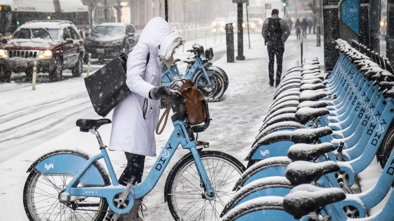 A woman clears off a Divvy bike as a winter weather advisory is issued for the Chicago area on Monday, Nov. 11, 2019, in Chicago. (Rich Hein / Chicago Sun-Times via AP)