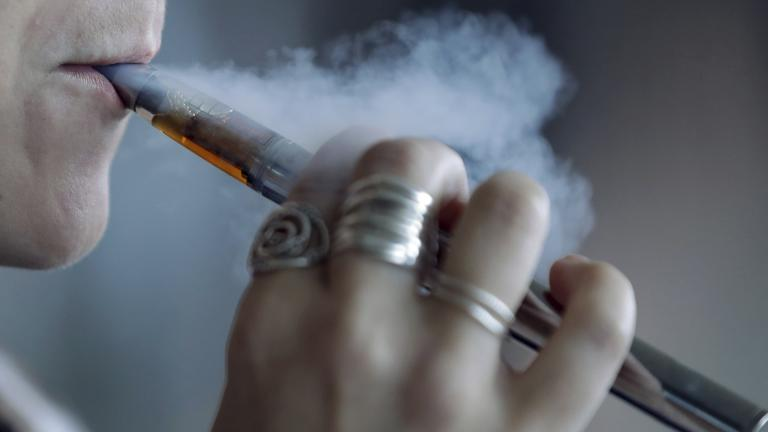 In this Friday, Oct. 4, 2019 file photo, a woman using a vaping device exhales a puff of smoke in Mayfield Heights, Ohio. (AP Photo / Tony Dejak, File)