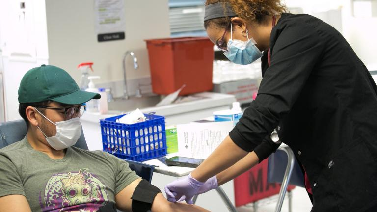 A Red Cross blood donor rolls up a sleeve to give blood during the COVID-19 outbreak at the Rockville Donation Center in Maryland. (Photo by Dennis Drenner / American Red Cross)