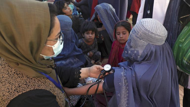 In this Aug. 10, 2021 file photo, an internally displaced woman from northern provinces, who fled her home due to fighting between the Taliban and Afghan security personnel, has her blood pressure taken after taking refuge in a public park in Kabul, Afghanistan. (AP Photo / Rahmat Gul, File)