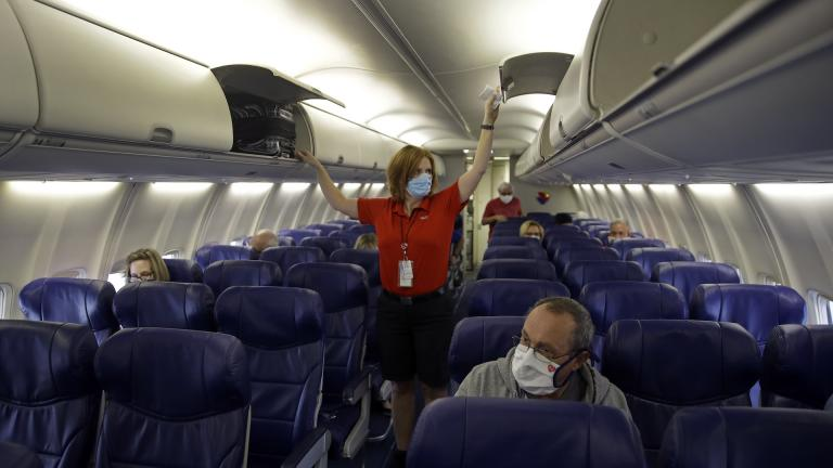 In this May 24, 2020, file photo, a Southwest Airlines flight attendant prepares a plane bound for Orlando, Fla. for takeoff at Kansas City International airport in Kansas City, Mo. About 40,000 workers in the airline industry are facing layoffs on Thursday, Oct. 1, unless Congress comes up with another aid package. (AP Photo/Charlie Riedel, File)