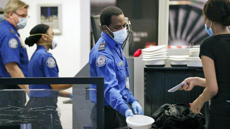 TSA officers wear protective masks at a security screening area at Seattle-Tacoma International Airport Monday, May 18, 2020, in SeaTac, Wash. (AP Photo/Elaine Thompson)