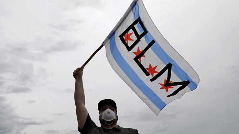 In this June 3, 2020, file photo, a protester waves a city of Chicago flag emblazoned with the acronym BLM for Black Lives Matter, outside the Batavia, Ill., City Hall during a protest over the death of George Floyd. (AP Photo / Nam Y. Huh, File)