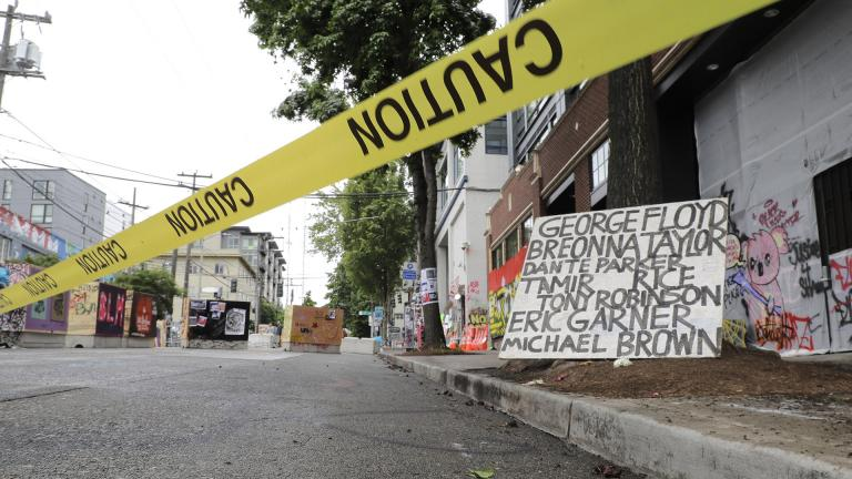 Caution tape is shown near a sign with the names of victims of police violence, Saturday, June 20, 2020, at the Capitol Hill Occupied Protest zone in Seattle. (AP Photo / Ted S. Warren)