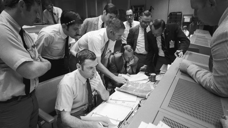 In this April 15, 1970 photo made available by NASA, a group of flight controllers gather around the console of Glenn S. Lunney, foreground seated, Shift 4 flight director, in the Mission Operations Control Room of Mission Control Center in Houston. (NASA via AP)