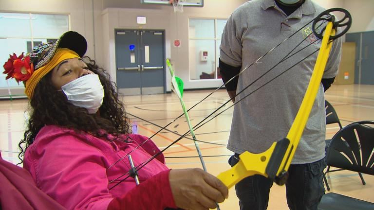 Babette Peyton demonstrates how she fits an arrow to a bowstring, an action called nocking in archery, at the Kroc Center Chicago on Nov. 19, 2020. (WTTW News)