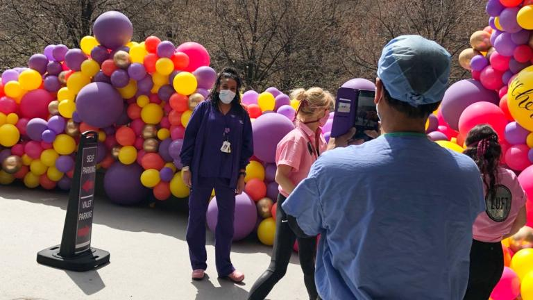 Respiratory therapist Jacob Thomas takes a photo of his colleague Felicia Smith in front of Luft Balloons' installation at Advocate Illinois Masonic Medical Center. (Patty Wetli / WTTW News)