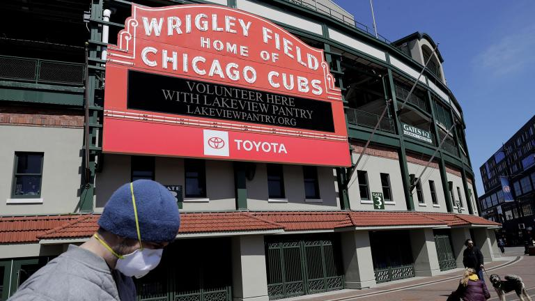 In this April 16, 2020 file photo, Wrigley Field's marquee displays Lakeview Pantry volunteer information in Chicago. The Chicago Cubs are instituting pay cuts because of the coronavirus crisis, but there will be no furloughs through the end of June. (AP Photo / Nam Y. Huh, File)