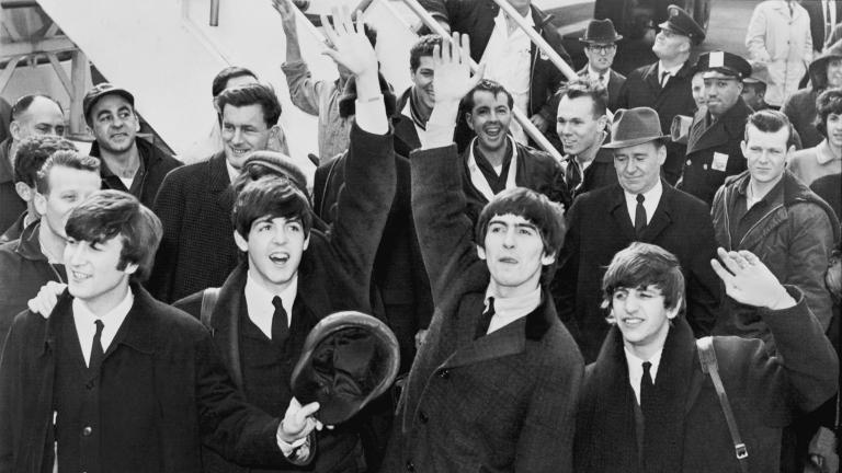 The Beatles wave to fans after arriving at Kennedy Airport in February 1964.