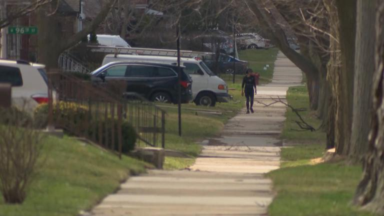 A lone figure walks along a residential street in the Beverly neighborhood of Chicago on March 30, 2020. (WTTW News)