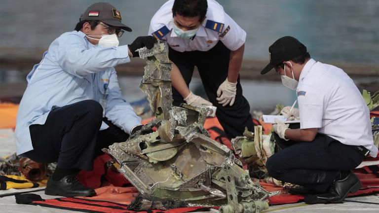 In this Jan. 21, 2021, file photo, investigators inspect a pieces of the Sriwijaya Air flight SJ-182 retrieved from the Java Sea where the passenger jet crashed on Jan. 9, at Tanjung Priok Port in Jakarta, Indonesia. A lawsuit filed in Seattle against Boeing alleges a malfunctioning autothrottle system on the older 737 jet led to the January crash of the Sriwijaya Air flight that killed all 62 people on board. (AP Photo / Dita Alangkara, File)