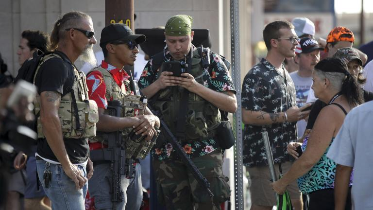 In this June 20, 2020 file photo, gun-carrying men wearing Hawaiian print shirts associated with the boogaloo movement watch a demonstration near where President Trump had a campaign rally in Tulsa, Okla. (AP Photo / Charlie Riedel, File)