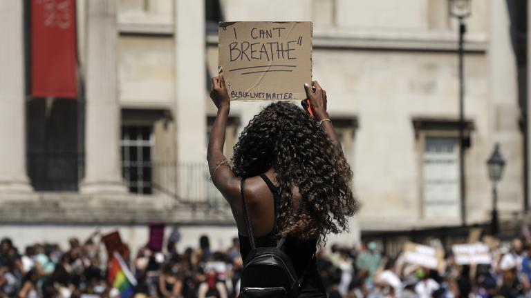 A woman holds up a banner as people gather in Trafalgar Square in central London on Sunday, May 31, 2020 to protest against the recent killing of George Floyd by police officers in Minneapolis that has led to protests across the U.S. (AP Photo / Matt Dunham)