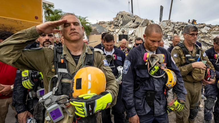 A member of the Israeli search and rescue team, left, salutes in front of the rubble that once was Champlain Towers South during a prayer ceremony, Wednesday, July 7, 2021, in Surfside, Fla. (Jose A Iglesias / Miami Herald via AP)